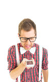Funny young nerd man yelling on the phone. Hipster guy with eyeglasses, bow tie and suspenders yelling during phone call. Isolated on white background Royalty Free Stock Images