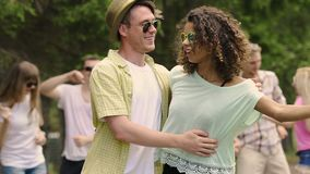 Funny young people dancing at outdoor party, handsome man hugging pretty woman stock video footage