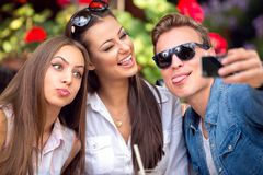 Funny young people taking selfie. In a cafe royalty free stock photos