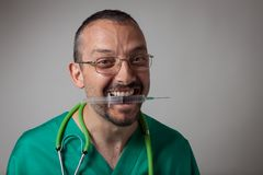 Funny young physician holding a syringe with his teeth. Funny young physician in green uniform holding a syringe with his teeth Stock Photography