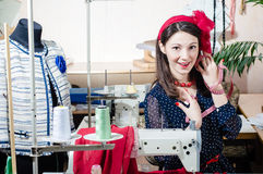Funny young pinup woman with sewing machine Royalty Free Stock Images