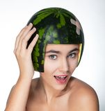Funny young pretty female in helmet - fresh melon Royalty Free Stock Photography