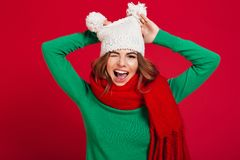Funny young pretty lady wearing hat and warm scarf. Photo of funny young pretty lady wearing hat and warm scarf standing isolated over burgundy background Stock Image
