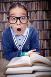 Funny young scientist, hustler with glasses in a library,educati. Funny,surprised young boy in a library with books on the table and sunglasses Stock Images