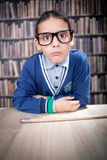 Funny young scientist, hustler with glasses in a library. Smart boy in the library by the bookshelves , educational concept, science Stock Photo