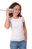 Funny young smiling girl listening on tin can phone. Royalty Free Stock Photography