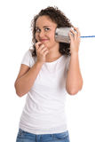 Funny young smiling girl listening on tin can phone. Royalty Free Stock Photo