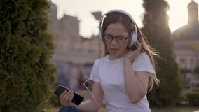 Funny young student sitting on the grass in the park and listening to music in big headphones. Girl singing along stock video