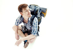 Funny Young tourist is sitting with backpack on white background. traveler is preparing for hike Royalty Free Stock Images