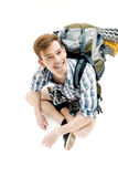 Funny Young tourist is sitting with backpack on white background. traveler is preparing for hike Stock Photo