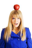Funny young woman with an apple on her head. Funny frightened young woman with an apple on her head Stock Photography