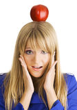 Funny young woman with an apple on her head. Funny frightened young woman with an apple on her head Royalty Free Stock Photo