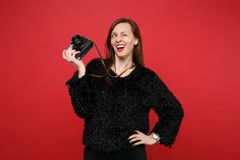 Funny young woman in black fur sweater blinking, looking up, holding retro vintage photo camera isolated on bright red. Wall background. People sincere emotions royalty free stock photo