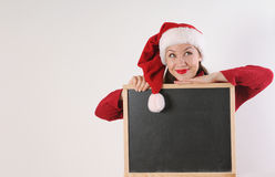Funny young woman with blackboard in santa hat on white backgrou Royalty Free Stock Image