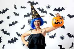 Funny young woman in a blue wig and witch`s hat holds Halloween pumpkin on a white background with black bats and stock photos