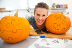 Funny young woman creating pumpkins for Halloween party Royalty Free Stock Images