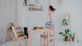Funny young woman dancing in kitchen wearing pajamas in the morning. Brunette girl in cheerful mood listens music. Royalty Free Stock Photography