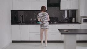 Funny young woman dancing in kitchen wearing pajamas in the morning. stock footage