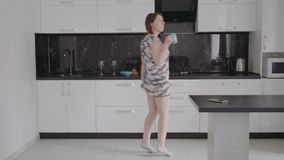 Funny young woman dancing in kitchen wearing pajamas in the morning. stock video