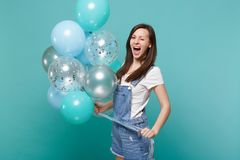 Funny young woman in denim clothes blinking, keeping mouth wide open, celebrating, holding colorful air balloons. Isolated on blue turquoise background royalty free stock photography