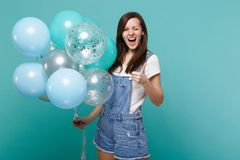 Funny young woman in denim clothes blinking showing thumb up, celebrating and holding colorful air balloons isolated on. Blue turquoise wall background royalty free stock image