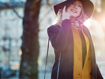 Funny young woman in elegant hat and scarf, walking. Portrait of the charming blonde on the street. Stock Photography