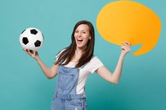 Funny young woman football fan cheer up support team with soccer ball, empty blank yellow Say cloud, speech bubble. Isolated on blue turquoise background stock photography
