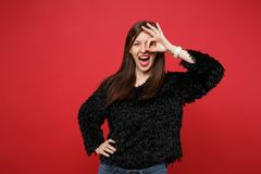 Funny young woman in fur sweater holding hand near eye, imitating glasses or binoculars, showing OK gesture isolated on. Red background. People sincere emotions stock photos