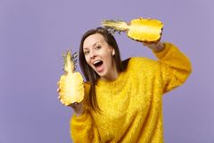 Funny young woman in fur sweater keeping mouth open holding halfs of fresh ripe pineapple fruit isolated on violet royalty free stock images