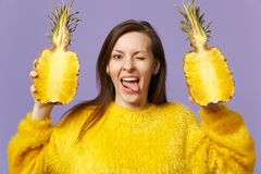 Funny young woman in fur sweater showing tongue holding halfs of fresh ripe pineapple fruit isolated on violet pastel royalty free stock image