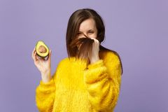 Funny young woman in fur sweater touching hair holding in hand half of fresh ripe green avocado isolated on violet. Pastel background. People vivid lifestyle stock images