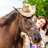 Funny young woman girl taking care of horse. Funny young woman girl taking care of brown horse. Female with animal outdoor royalty free stock photos