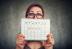 Funny young woman in glasses hiding behind a periods calendar and looking at camera royalty free stock image