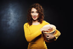 Funny young woman grabbing handful of popcorn with cheerful smile. Looking straight at camera Royalty Free Stock Photos