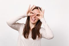 Funny young woman in light clothes holding hands near eyes, imitating glasses or binoculars showing tongue isolated on royalty free stock photos