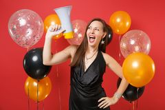 Funny young woman in little black dress celebrating, looking up, holding megaphone on red background air balloons. St