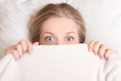 Funny young woman lying in bed under blanket Royalty Free Stock Photography