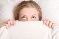 Funny young woman lying in bed under blanket and dreaming Stock Images