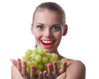 Funny young woman offer green grapes isolated Stock Images