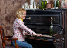 Funny young woman playing shabby retro piano. Indoors Stock Image