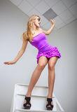 Funny young woman posing on ladder Royalty Free Stock Photography