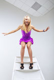 Funny young woman posing on ladder Stock Photos