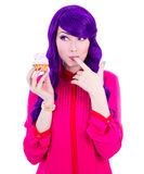 Funny young woman with purple hair holding cupcake with pink cre Royalty Free Stock Photo