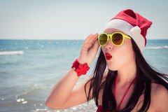 Funny young woman  in Santa Claus hat and sunglasses Royalty Free Stock Photography