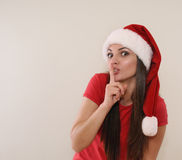 Funny young woman in Santa hat having a secret from you for Chri Royalty Free Stock Image