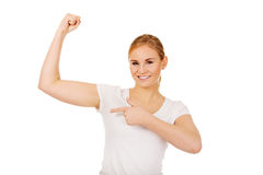 Funny young woman showing her muscles Stock Photos