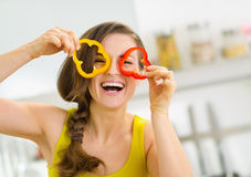 Funny young woman showing slices of bell pepper Stock Photography