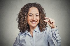 Funny young woman showing small amount size gesture with hand. Closeup portrait, funny young curly brown hair woman showing small amount gesture with hand Royalty Free Stock Image