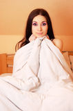 Funny young woman sitting in bed. Funny young brunette sitting shocked in her bed in the morning Stock Photo