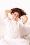 Funny young woman sitting in bed Stock Photo